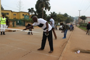 Fred Tukahirwa lays out masking tape ahead of commencing the painting